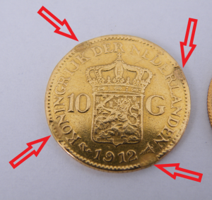 Beschadigde gouden munt klemsporen